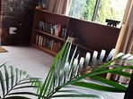 Sunroom next to swimming pool with seperate entrance and bookshelf full of books for you to read.