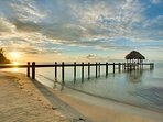 sunset over large 150 foot pier with palapa and swim deck