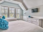 This bedroom features a TV and lots of natural light.