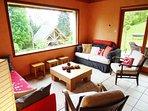 Salon confortable avec grande baie vitrée et vue sur la chaîne de Belledonne