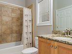 The guest bathroom has gorgeous granite, upgraded Delta brushed nickel fixtures and a tile shower/tub combination