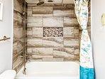 The Guest Bath offers a tub and overhead rain shower head