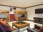 Den with two sets of twin bunk beds, TV, kitchenette, and half bath.