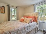 Bright coral pillows add the perfect pop of color to this second bedroom.