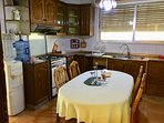 big kitchen with dining table, stove, microwave, fridge, electric kettle, cold water dispenser