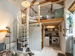 Climb the spiral staircase to the mezzanine bedroom set under the eaves