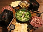 Eating raclette with traditional table top barbecues