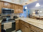 Well equipped kitchen has granite countertops, full size appliances, everything needed for meal preparation.