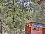 The private hot tub offers a serene scene surrounded by pine trees.