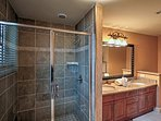 The second full bathroom has a walk-in glass-enclosed shower.