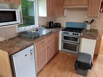 Kitchen area with toaster microwave gas cooker cooking utensils plates cutlery kettle and fridge