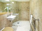 The walk in ensuite wet room of the ground floor Garden Room with a shower and glass screen