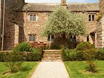 The patio area leading to the gardens, yew hedges, climbing roses, sandstone, terraces