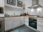 A kitchen with microwave, washer/dryer, oven, cooktop, with cookware and tableware