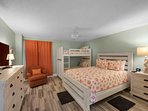 Guest bedroom with a queen sized bed and twin bunk beds
