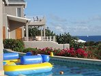 The balconies of the master bedroom and bedrooms at the pool level. View sail boat in the Caribbean.
