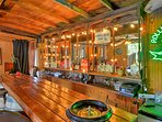Fix yourself a drink at the long wooden bar.
