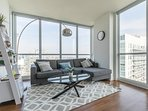 Bright and modern living room with floor to ceiling windows and a beautiful view of the city skyline
