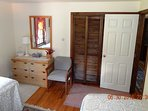 Guest Bedroom NW corner.  Ample storage with bureau and closet.  chair.
