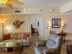 The tropically decorated great room has a queen sleeper sofa and a comfy leather recliner.