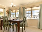 The dining room is a sunny converted porch with windows all around and a colorful dining set for 6.
