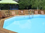 Swimming pool with trampoline in the background also for guest use