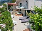 Lower terrace with the hot tub, solar shower and the sun bath area; view on the main terrace