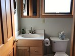 Full bathroom with tiled floor and tub surround.