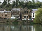 Village millpond showing the famous Scarthin book shop and cafe