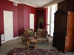 Red guest suite sitting area. Armoire with private tv.