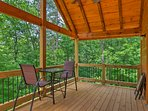 Relax on the spacious back deck during your stay at this vacation rental cabin!