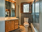 Sliding glass doors frame the walk-in shower in this full bathroom.