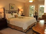 Master bedroom with king bed, wide arm chair, credenza, stylish lamps. Large flat screen TV. Italian wood grain tile...