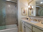 Ensuite bathroom to guest bedroom #1 features a combination tub shower and marble finishes
