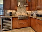 Enjoy premium Viking appliances like the wine fridge that nicely accent the natural textures of the stone tile and...