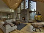 Another view of the luxurious living room with gas fireplace, flatscreen tv and beautiful floor to ceiling windows