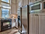 The kitchen features a stainless steel undermount sink, stainless steel refrigerator, and lots of nice cabinet storage.