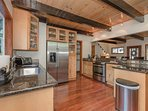 This modern kitchen comes furnished with maple cabinetry, exposed beams, and stainless steel appliances.