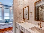 This bathroom with double vanity and walk-in shower is located on the first floor by the reading nook