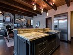 The professional kitchen is large enough to accommodate multiple chefs.