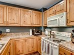 The kitchen is fully appointed with an oven, microwave, refrigerator, and dishwasher