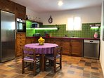Kitchen with electric stove, oven, microwave, toaster, dishwasher, kettle and coffee machine.