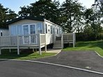 Luxury Caravan with French doors opening onto an enclosed veranda.  Large decking and Hot tub.