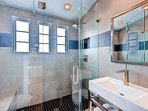 The shared guest bathroom is adorned with a vanity and a walk-in shower