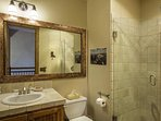 The shared bathroom on the main level features a single sink and a walk in shower.