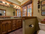The master en-suite bathroom has two sinks and gorgeous wood cabinetry.