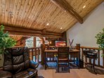 The lofted office space overlooking the living area allows the king or queen of the cabin to keep an eye on their...