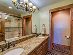 This shared guest bathroom has shower/tub combo and dual sinks.