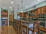 The spacious kitchen with its breakfast bar and stainless-steel appliances can double as your welcome center.