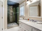The private bathroom to Guest Bedroom #3 features a marble vanity and a walk-in shower.